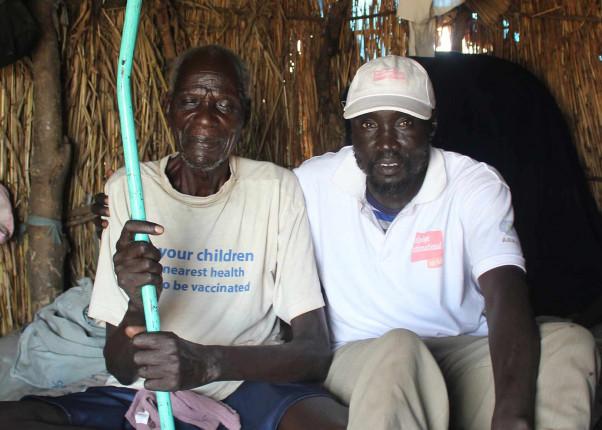 Ein von Hunger gezeichneter afrikanischer alter Mann mit einem HelpAge Mitarbeiter