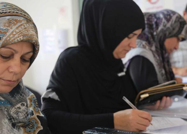 Libanesische Frauen und Männer beim Ausfüllen von Unterlagen