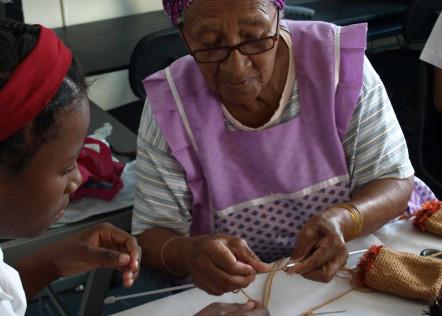 Ältere afrikanische Frau erklärt jüngerem Mädchen das Stricken