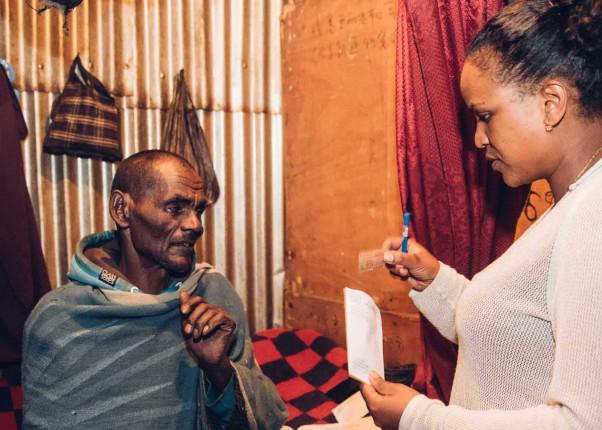 Eine hilfebedürftiger Mann empfängt Unterlagen durch eine Mitarbeiterin