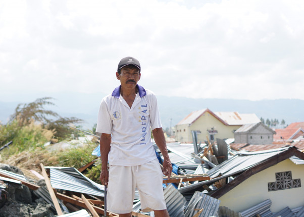 Ein Mann steht in den Trümmern