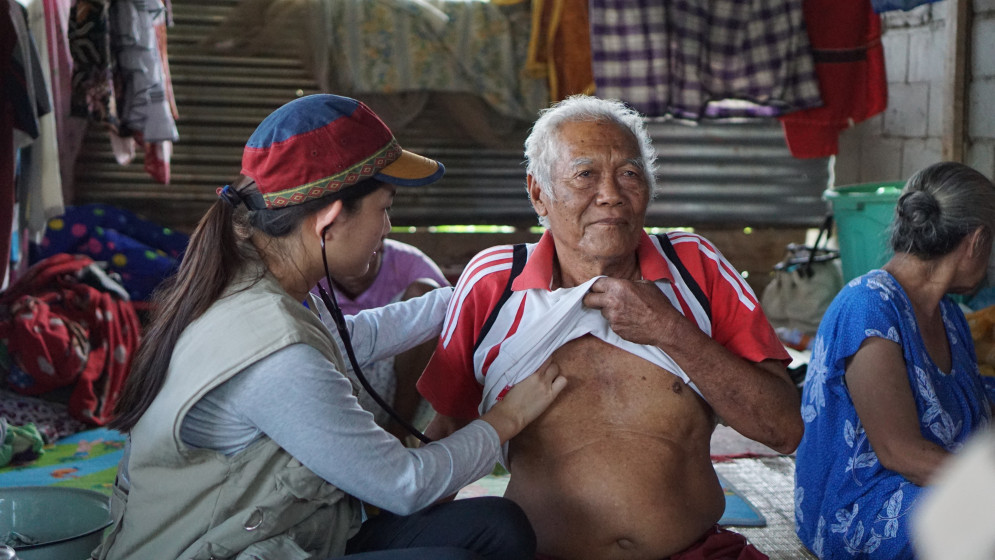 Eine Helferin versorgt einen alten Mann