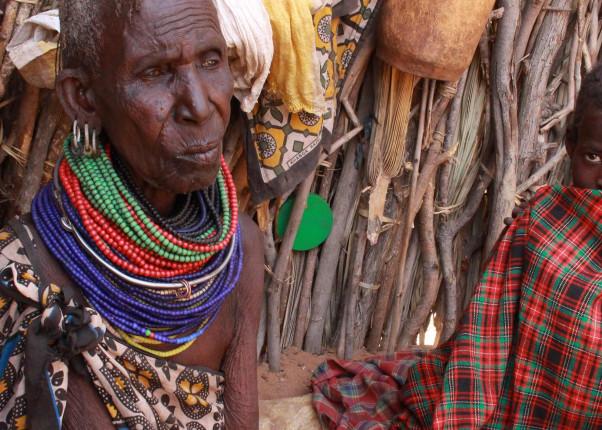 Eine alte Dame und ein Kind sitzen vor einer Hütte aus Ästen