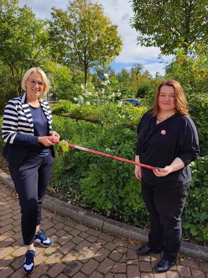 HelpAge-Geschäftsführerin Sonja Birnbaum überreicht der künftigen Oberbürgermeisterin von Osnabrück Katharina Pötter zum Weltaltentag einen bunt gestalteten Gehstock.